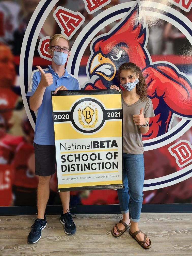 2 students giving thumbs up signs and holding a poster that says  National Beta School of Distinction 2020-2021